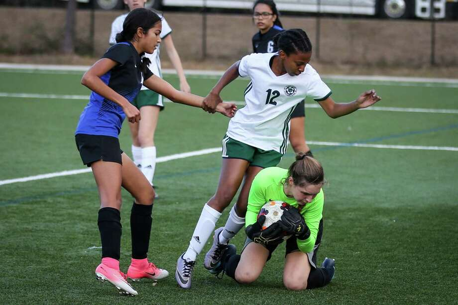 The Woodlands' Kayla Fowler (12) holds onto New Caney's Angela Romero (4) to avoid falling over New Caney's Kali Helms (1) during the girls soccer game on Saturday, Jan. 20, 2018, at the Gosling Sports Complex. (Michael Minasi / Houston Chronicle) Photo: Michael Minasi, Staff Photographer / Houston Chronicle / © 2017 Houston Chronicle