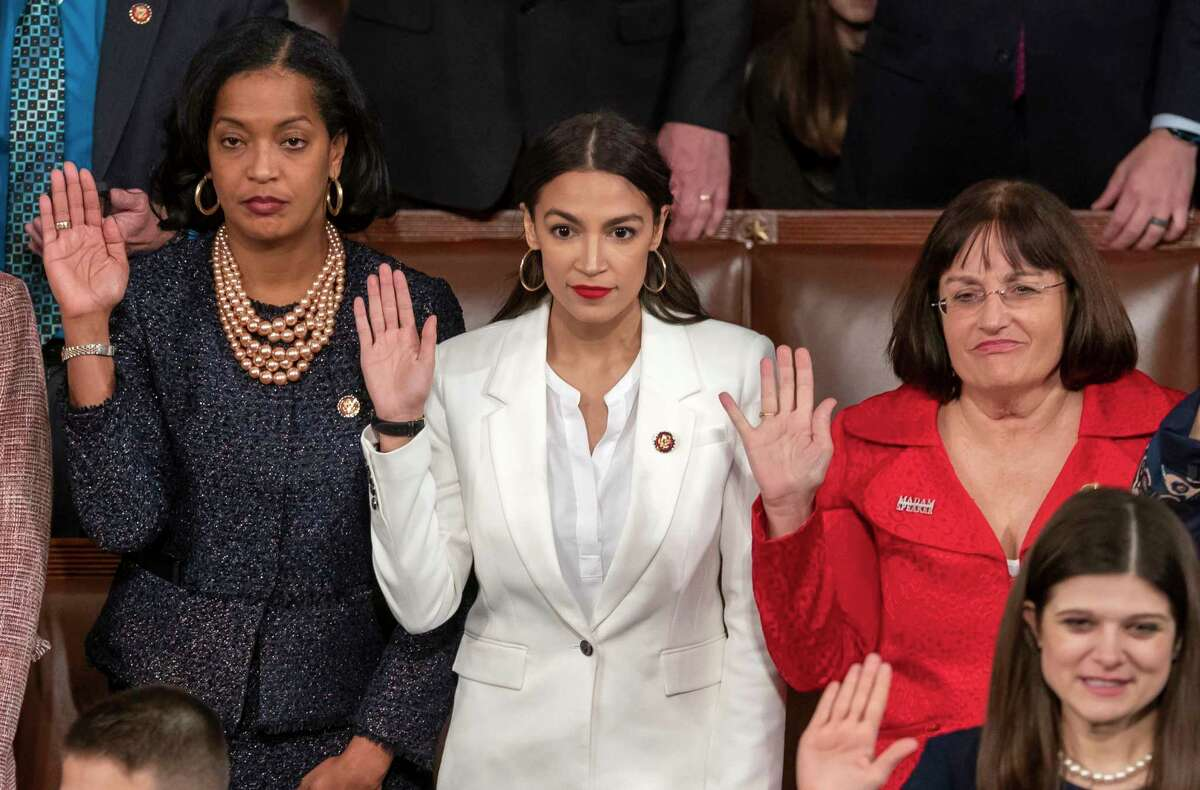 Rep. Alexandria Ocasio-Cortez, center, a freshman Democrat representing New York's 14th Congressional District, is flanked by Rep. Jahana Hayes, D-Conn., left, and Rep. Ann McLane Kuster, D-N.H., right, as they are sworn in on the opening day of the 116th Congress at the Capitol in Washington, Thursday, Jan. 3, 2019. (AP Photo/J. Scott Applewhite)