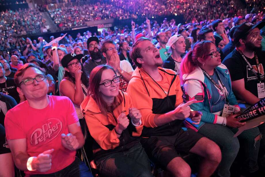 FILE - In this July 28, 2018 file photo, Philadelphia Fusion fans react as the London Spitfire takes the lead during the Overwatch League Grand Finals competition at Barclays Center in the Brooklyn borough of New York. Most professional esports are devoid of female players at their highest levels, even though 45 percent of U.S. gamers are women or girls. Executives for titles like League of Legends and Overwatch say they are eager to add women to pro rosters, but many female gamers say they're discouraged from chasing such careers by toxic behavior and other barriers. (AP Photo/Mary Altaffer, File) Photo: Mary Altaffer / Copyright 2018 The Associated Press. All rights reserved.