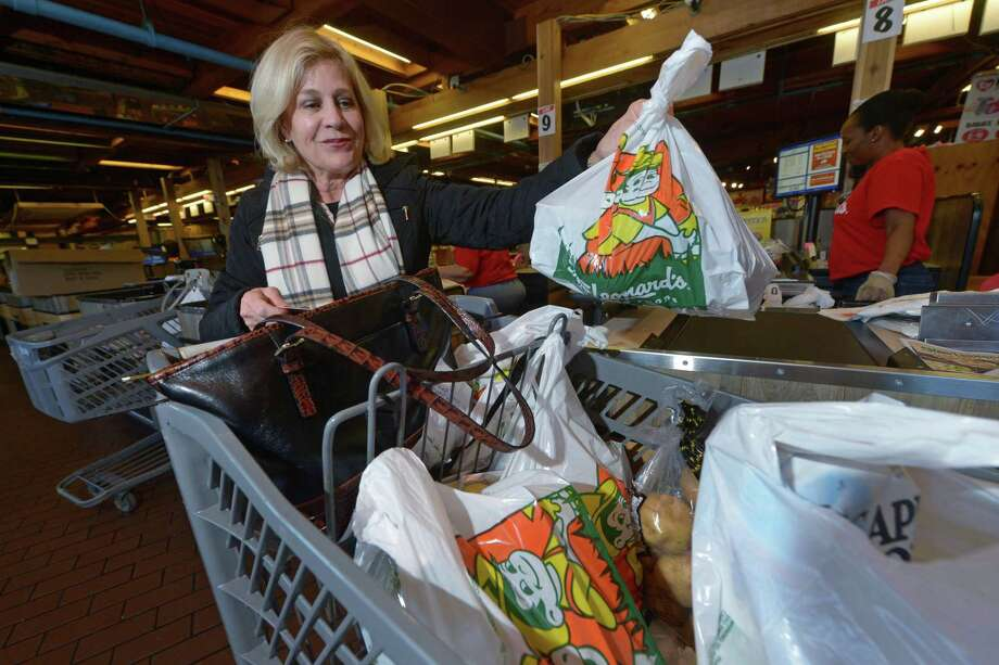 Customer Mary Burner, of Westport, loads groceries in Stew Leonard's iconic plastic bags into her cart at the Norwalk store. Photo: Erik Trautmann / Hearst Connecticut Media / Norwalk Hour