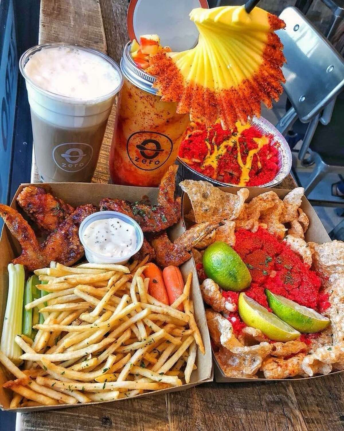 Pictures are some wings with a side of fries, XXTRA Flamin Hot Chicharrones, XXTRA Flamin Hot Elote and the popular Mangonada with chunks of mango on the straw.