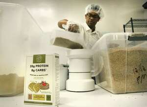 Yoni Medhin, prepares to grind spent barley into flour to be used in a pancake mix.