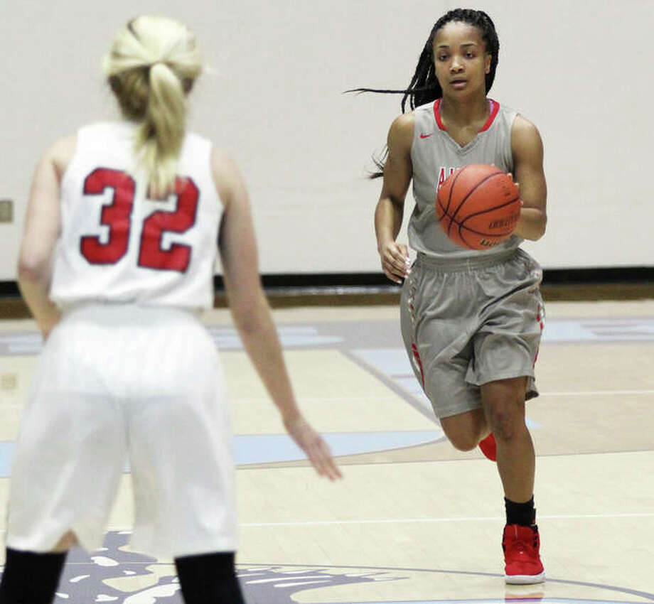 Alton's Jayla Fox (right) brings the ball upcourt during a Redbirds win over Calhoun last Saturday at the Jersey Tournament. Fox scored a team-high nine points Thursday night in Alton's SWC loss at Belleville West. Photo: Greg Shashack / The Telegraph
