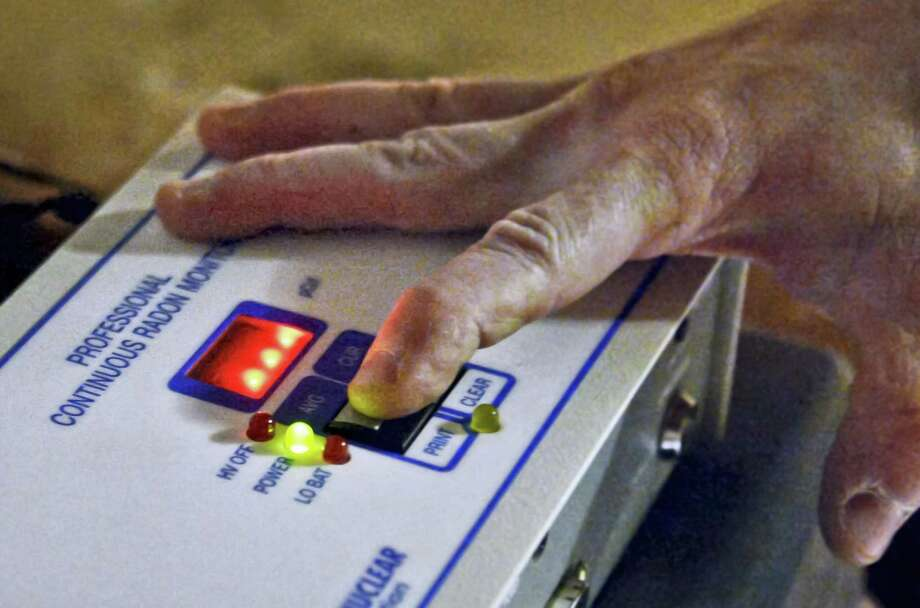 An inspector prepares a radon monitor in the basement of a home for sale. Photo: File Photo / 40043527A