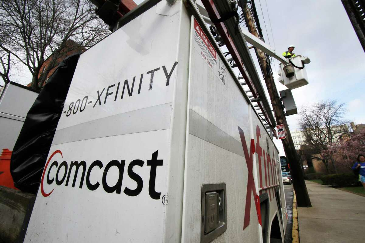 FILE- In this March 27, 2017, file photo, a Comcast worker performs work in Pittsburgh. NEXT: Who needs cable? See what original series and movies are coming to Netflix this month.