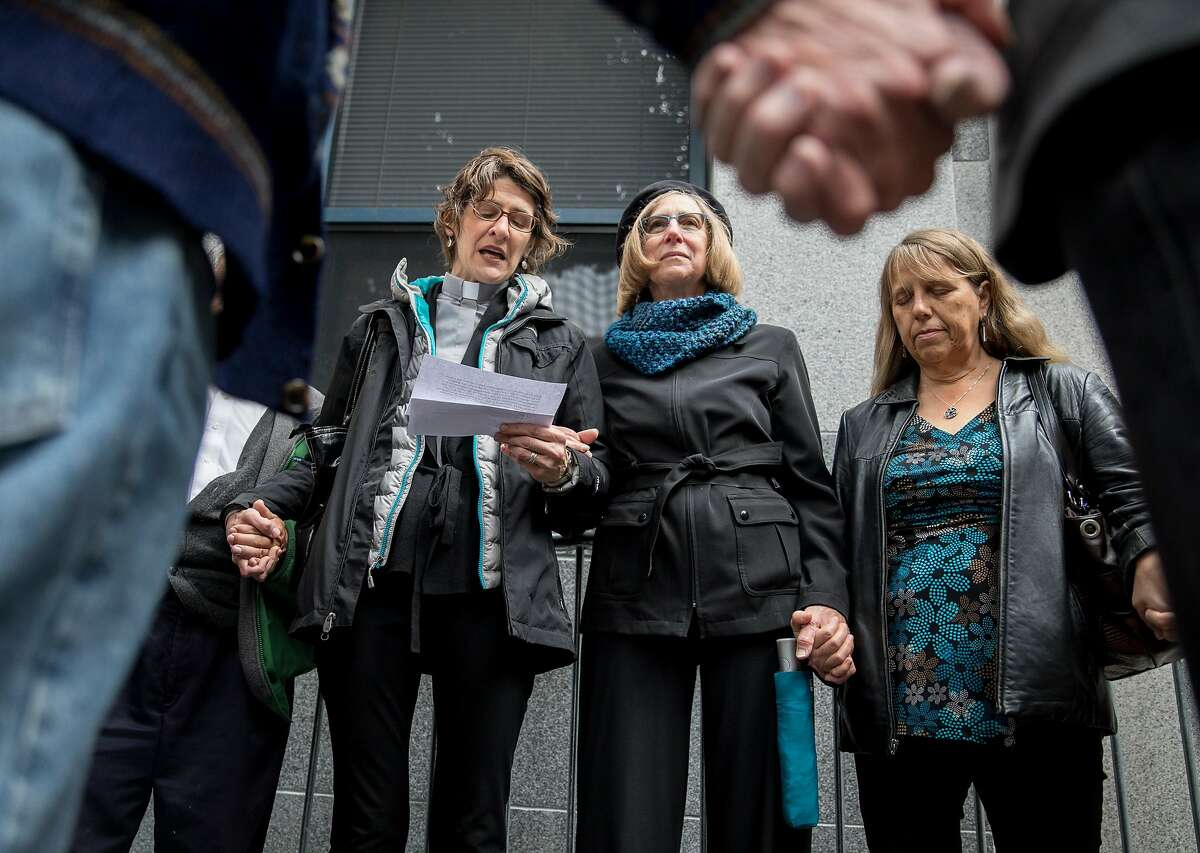 (From left) Interim Minister Tovis Page, faith-based leader Kaye Bonney, and church member Barbara Du Bond join hands in prayer outside of the U.S. Citizen and Immigration Services building in San Francisco, Calif. Wednesday, Nov. 28, 2018 before entering to support undocumented immigrants during their immigration court hearings.