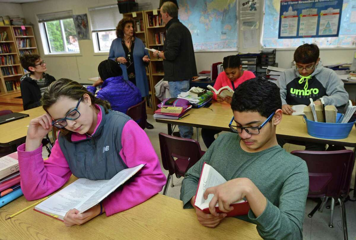 Side by Side Charter School 8th graders Grace Galeano and Sam Aguilar read during their humanities class Friday, April 7, 2017, at the school in Norwalk, Conn. The School is celebrating its 20th anniversary and has announced construction plans for a new school building to house their middle school students.