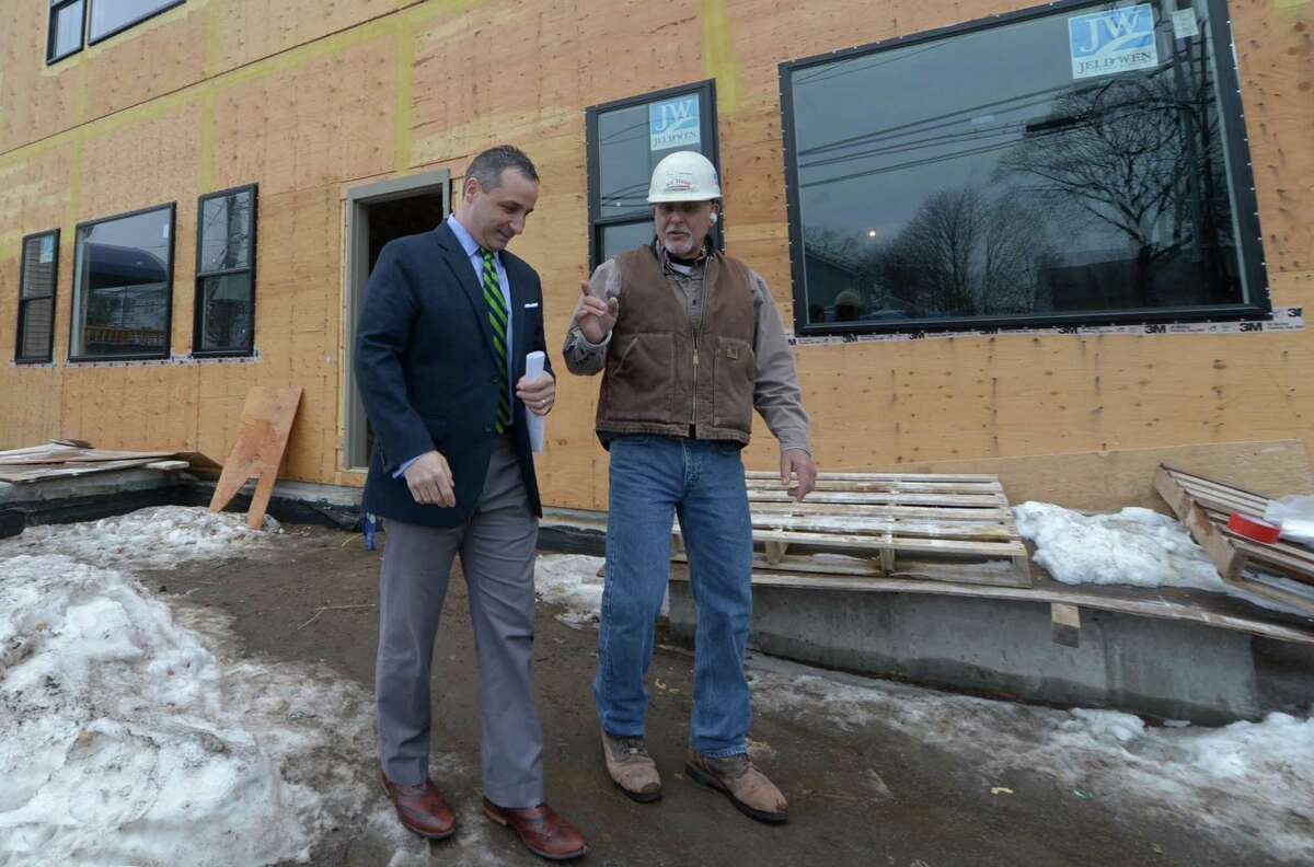 Side by Side School Director Matthew Nittoly and A.V. Tuchy job superintendent Neil Esposito discuss the construction on Side by Side Charter School's new building Thursday, January 11, 2018, at 10 Chestnut St. in Norwalk, Conn. The Connecticut General Assembly has included funding in the recently approved state budget to help complete construction of a permanent middle school facility for Side by Side Charter School which currently runs out of temporary, modular buildings. Construction on $3.6 million project began over the summer in 2017, and the new 11,600-square-foot building expected to be completed in time for the 2018-19 school year.