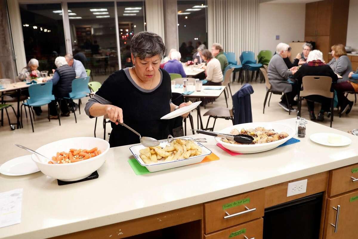 Leslie Watson-Hollinsead serves herself dinner at Phoenix Commons in Oakland, Calif. on Wednesday, December 5, 2018.