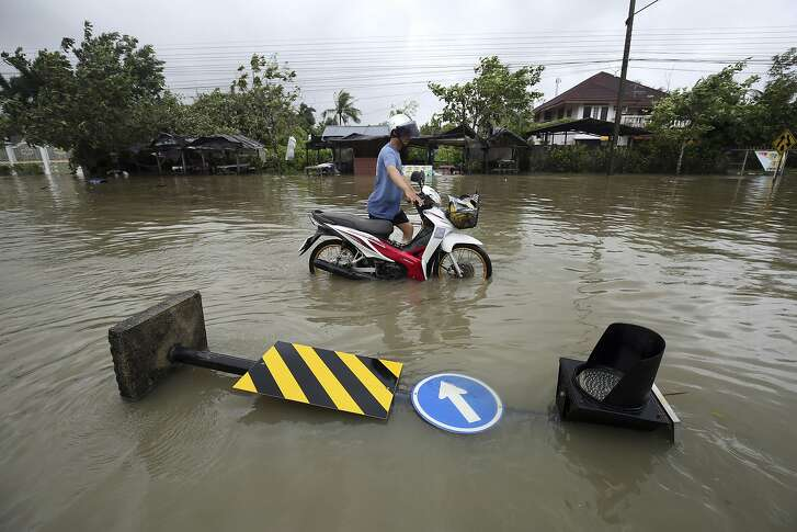 Thai people push a motorcycle through floodwater from Tropical Storm Pabuk, Friday, Jan. 4, 2019, in Pak Phanang, in the southern province of Nakhon Si Thammarat, southern Thailand. Rain, winds and surging seawater are striking southern Thailand as a strengthening tropical storm nears coastal villages and popular tourist resorts. (AP Photo/Thanis Sudto)