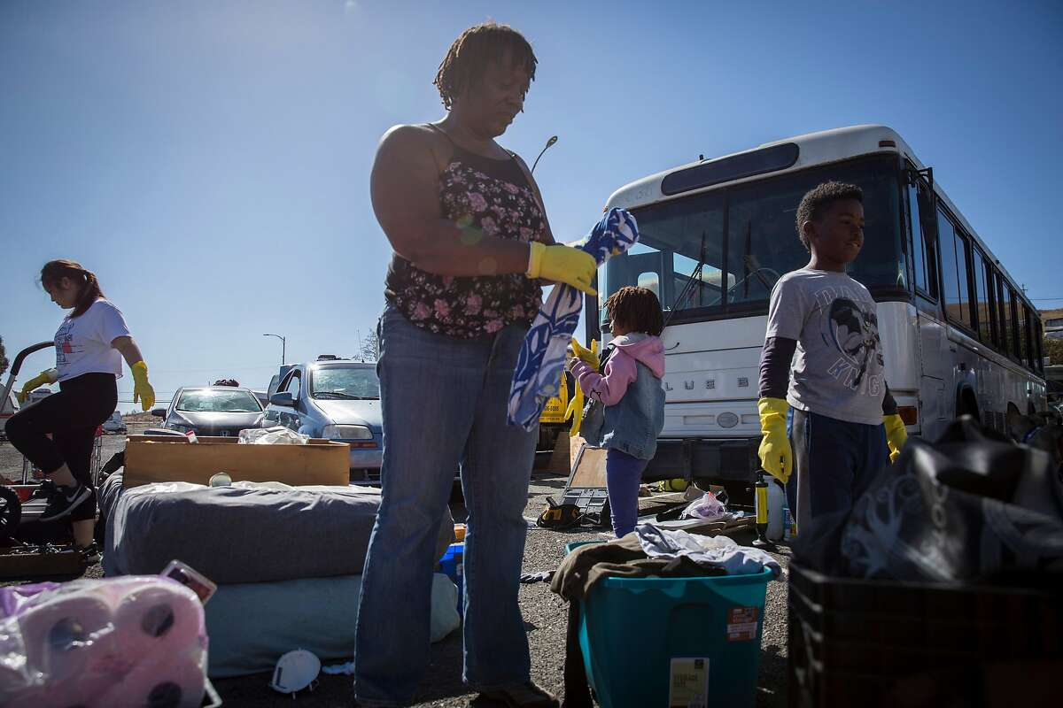 Constance Johnson, center, works with her two children and a group of volunteers from UC Berkeley to clean out her bus in Vallejo on Sunday, October 14, 2018. Tiny House in My Backyard, an organization run by UC Berkeley students, works with other organizations to build Johnson's bus into a tiny house.