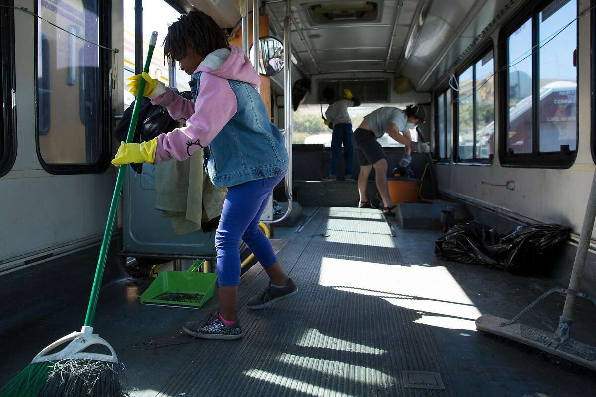 Constance Johnson's two children work with a student volunteer from UC Berkeley to clean out Johnson's bus in Vallejo on Sunday, October 14, 2018. The Tiny House in My Backyard plans to finish converting Johnson's bus into a tiny house in February.