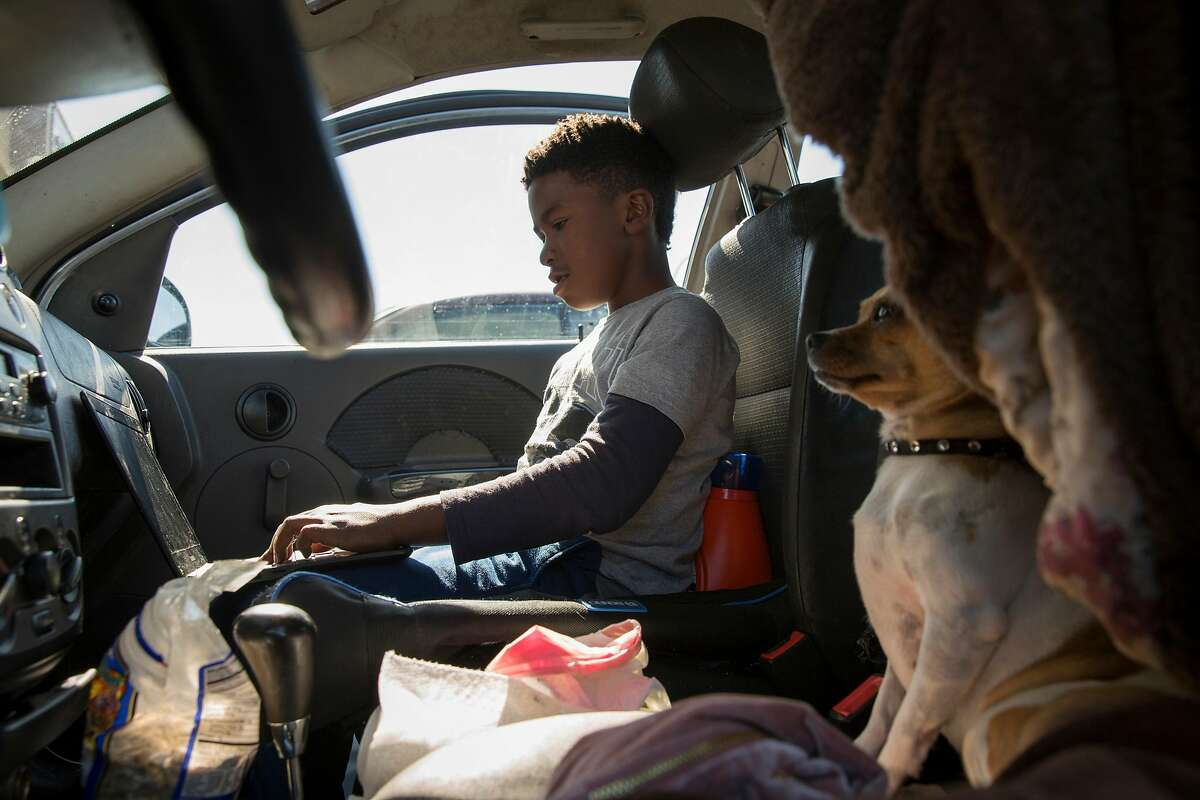 Constance Johnson's son, 11, plays video games in a sedan with his dog Tinkerbell sitting next to him in Richmond on Saturday, Oct. 13, 2018. Tinkerbell lives in this car when the family stays in the shelter.