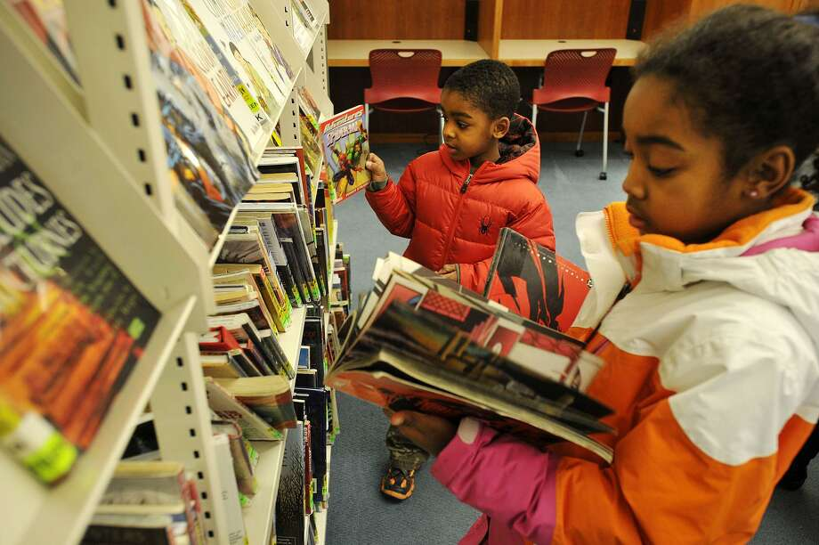 """Evan Myers and his sister, Olivia, look at comic books at the Ferguson Library on Jan. 5, 2014. According to their mother, the two became interested in comic books after watching the movie, """"The Avengers."""" Photo: Jason Rearick / File Photo / Stamford Advocate"""