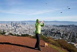 Catherine Vowles captures a 360-degree panoramic photo after climbing to the south summit of Twin Peaks with her dog Bandito in San Francisco, Calif. on Tuesday, Jan. 1, 2019.