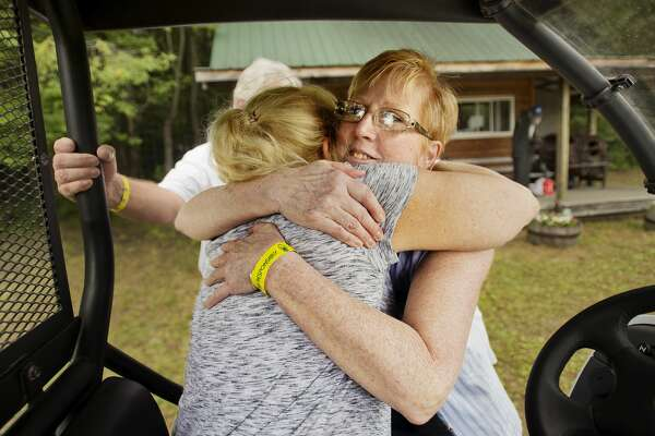 Lisa Burrows of Davison, right, hugs Kris Carr, left, during the Salt River Bluegrass Festival on Friday, July 27 in Oil City. The weeked marked the last bluegrass festival for organizers George and Kris Carr, as George Carr was extremely ill, having been diagnosed with pancreatic cancer earlier in the month. (Katy Kildee/kkildee@mdn.net)
