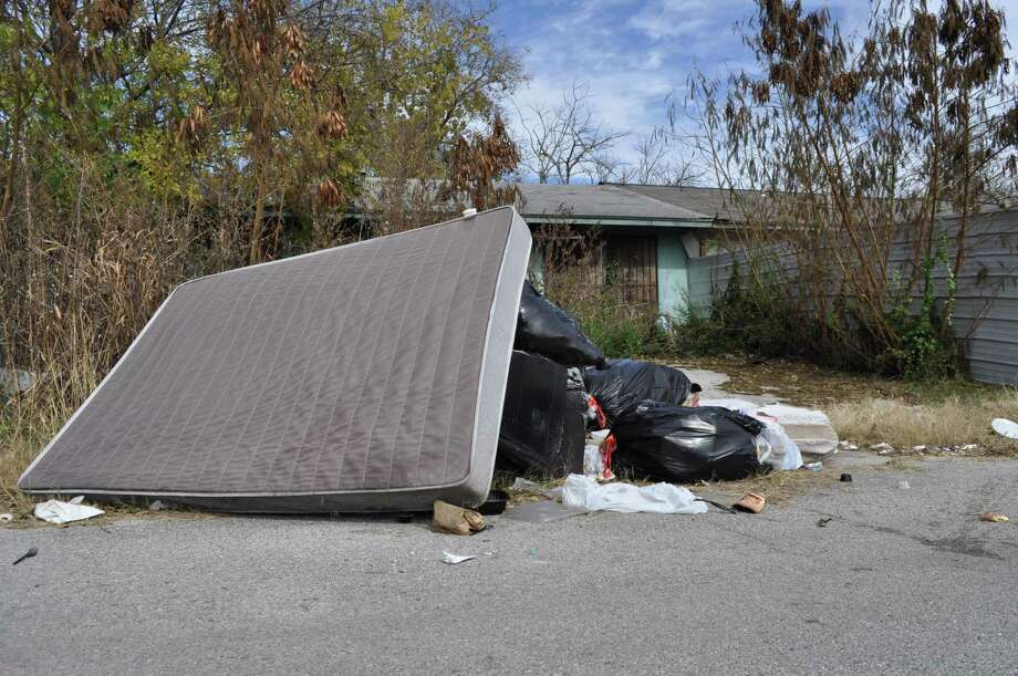 Trash piles up in The Glen in Northeast Bexar County. The city helped Bexar County provide trash service in the nearby Camelot II. And yet the county is claiming it's helpless to mandate trash service. Photo: Josh Brodesky /Staff