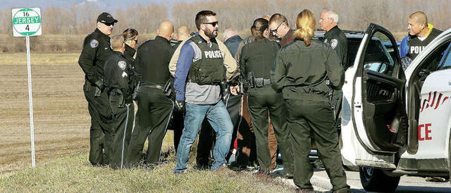 Some of the nearly 20 police officers from Alton, Grafton, Jersey County Sheriff's Department and the Illinois Conservation Police converge of the handcuffed driver after Thursday's chase. Photo: John Badman | The Telegraph