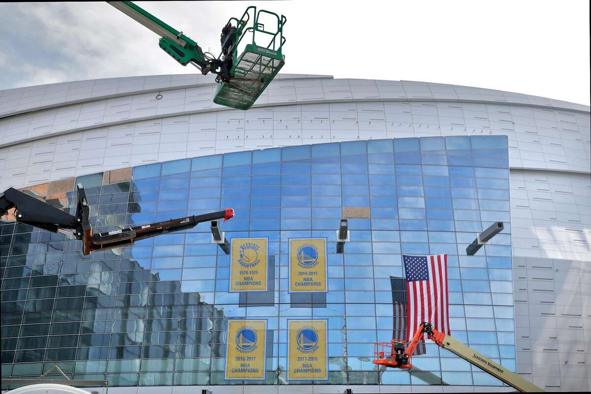 Constructions cranes surround the four Warriors NBA championship banners hanging on the outside at the new Chase Arena still under construction in San Francisco on Friday, Jan. 4, 2019. The Warrior will open their 2019-2020 season in the new facility.
