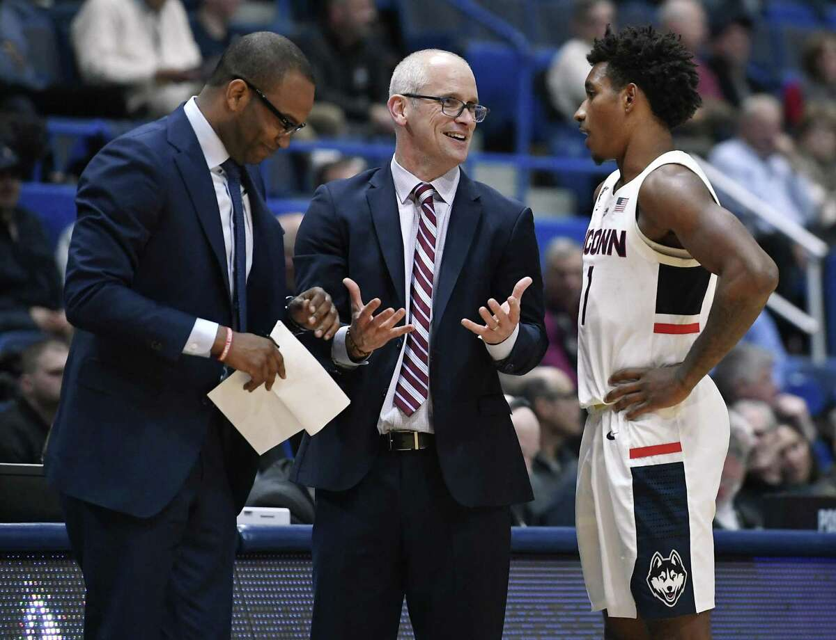 UConn head coach Dan Hurley, center, talks with Christian Vital, right as assistant coach Kimani Young, left, listens.