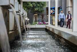 Pedestrians walk past a fountain located along a small urban trail nestled between Mission and Howard streets and Main and Spear streets in San Francisco, Calif. Tuesday, Dec. 18, 2018.