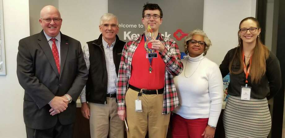 "The Connecticut Food Bank presented its 2018 Commitment and Service Award to KeyBank Mail Assistant James Trimble, at a special celebration event held in KeyBank's New Haven Main branch Nov. 30. Trimble has served as a volunteer at the food bank since 2005; this year, he will complete more than 50 personal volunteer hours at the nonprofit. In 2012 he was recognized by the food bank as a Volunteer Hunger Action Hero for his years of engagement with the food bank. In 2013, Trimble initiated the ""Super-Size Me"" food drive to help neighbors impacted by Super Storm Sandy and continued this effort since then, raising more than $15,000 in cash donations and thousands of pounds of donated food. From left are KeyBank Market President Jeff L. Hubbard; Connecticut Food Bank President and CEO, Bernie Beaudreau; Trimble; Trimble's manager Brenda Holman; and Connecticut Food Bank Corporate Development Manager Mia Freedenfeld. Photo: Contributed Photo"