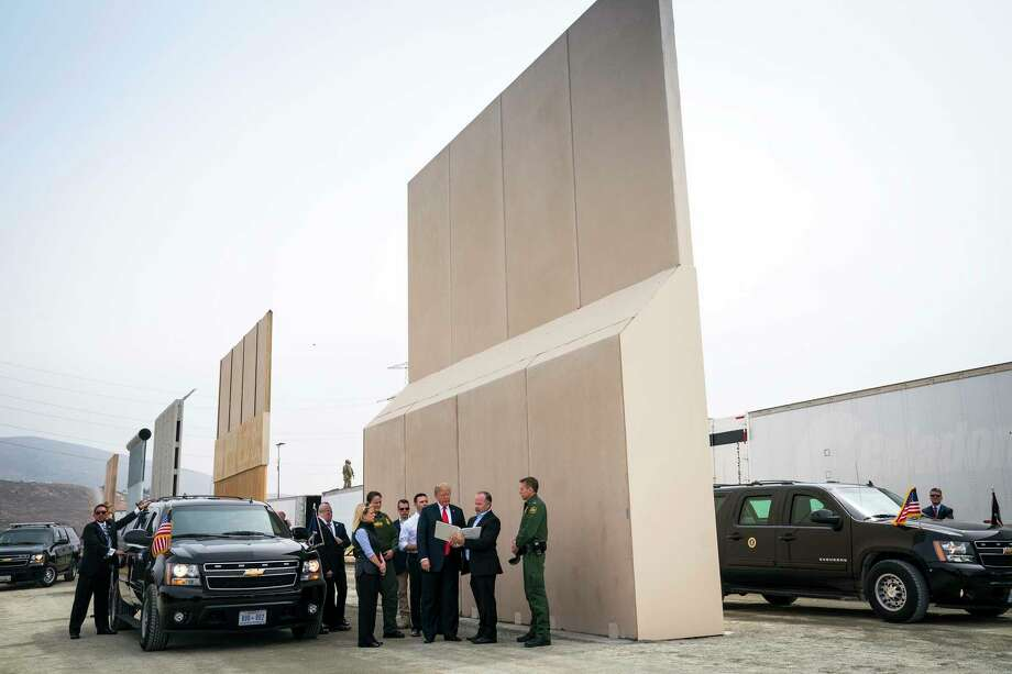 "FILE -- President Donald Trump views border wall prototypes in the border neighborhood of Otay Mesa near San Diego, March 13, 2018. ""The president still says 'wall,'"" John Kelly, the outgoing White House chief of staff, said in an interview with the Los Angeles Times. ""But we left a solid concrete wall early on in the administration."" His comments come as a partial government shutdown caused by a fight over a border barrier drags into a second week. (Doug Mills/The New York Times) Photo: DOUG MILLS / NYTNS"
