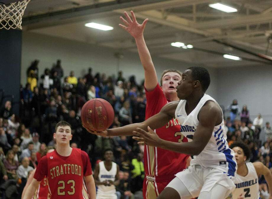 Bunnell's Elijah Alexandre lays up the ball as Stratford's Preston Williams defends on Friday in Stratford. Photo: Christian Abraham / Hearst Connecticut Media / http://connpost.com/