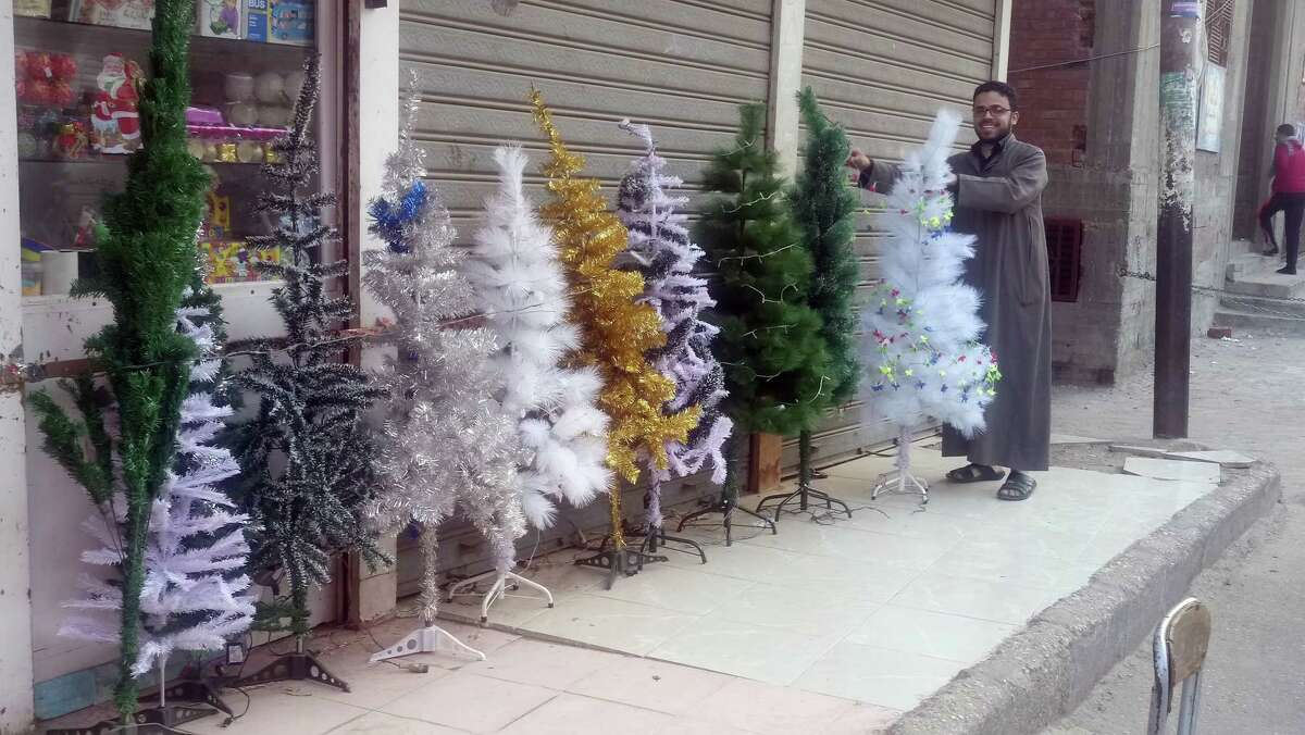 Fady Hadny / Religion News Service A villager wearing a traditional peasant galabiya gown inspects Christmas trees in El Kosheh, Egypt, on Dec. 18, 2018.