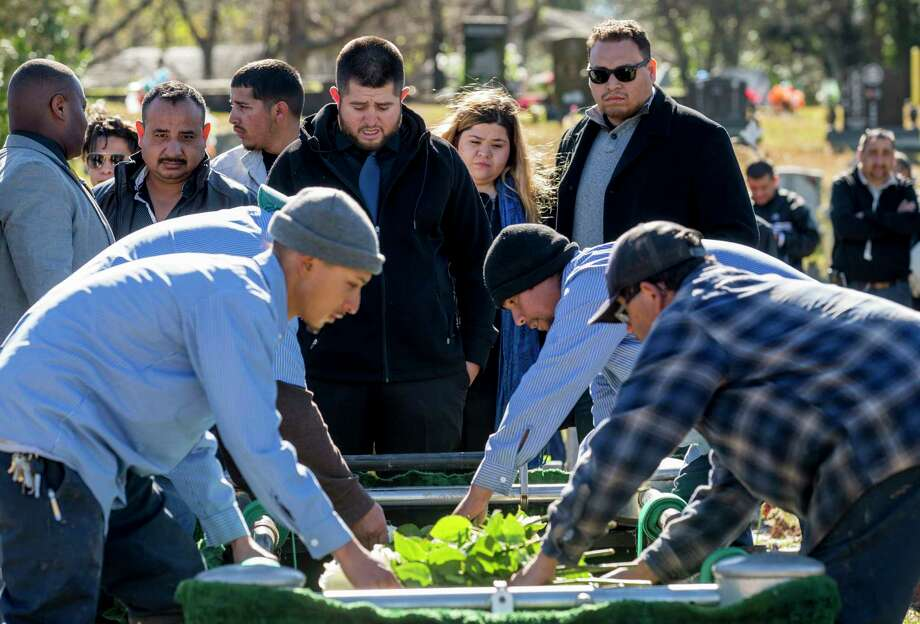Luis Gaspar, 24, center, and sister Jessica Gaspar, 20, watch as workers lower their mother's casket during burial services at the Hollywood Cemetery on Friday, Jan. 4, 2019. Silvia Zavala was struck by a teenage driver who was allegedly speeding after being chased by a motorist. Photo: Godofredo A. Vasquez, Staff Photographer / 2018 Houston Chronicle