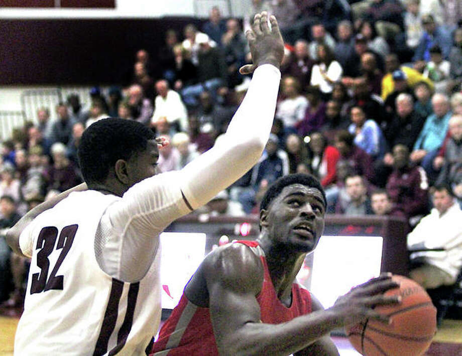 Alton's Charles Miller (right) looks to shoot while Belleville West's 6-foot-7 E.J. Liddell defends during a Southwestern Conference boys basketball game Friday night in Belleville. Photo: Greg Shashack | The Telegraph