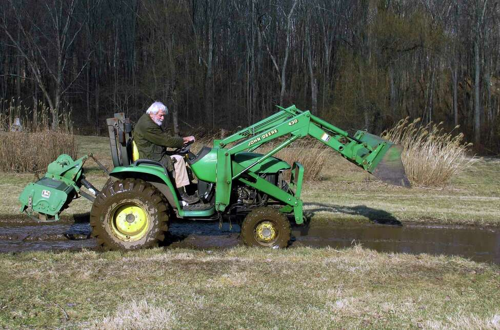 Edward Cook, widower of the late famed herbalist Adelma Grenier Simmons, operates a tractor at the Caprilands herb farm, Thursday, Jan. 3, 2019, in Coventry, Conn. Simmons, who died in 1997 at age 93, is credited with reintroducing and popularizing the use of herbs in American cooking. Cook, accused of failing to maintain the property, is fighting an eviction order. (AP Photo/Dave Collins)