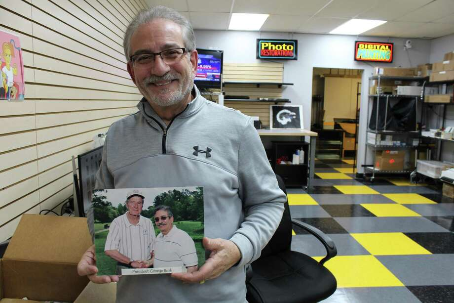 Khalaf holds of photo of him shaking hands with Former President George H.W. Bush at the Kingwood Country Club in the early 2000's. Photo: Kaila Contreras