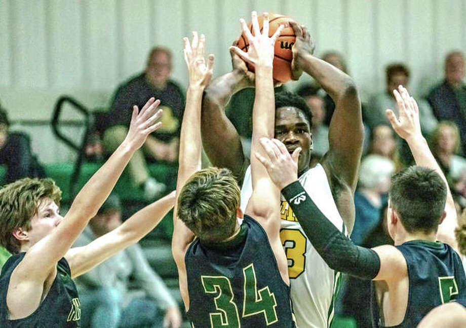 Metro-East Lutheran's DeMonte Bean (43) scans for a passing lane as he's swarmed by three Father McGivney Catholic defenders Friday night during the Knights' 54-34 win over the Griffins. Bean put up nine points in the contest. The win improves Metro-East's record to 10-7 on the season. Photo: Nathan Woodside/The Intelligencer