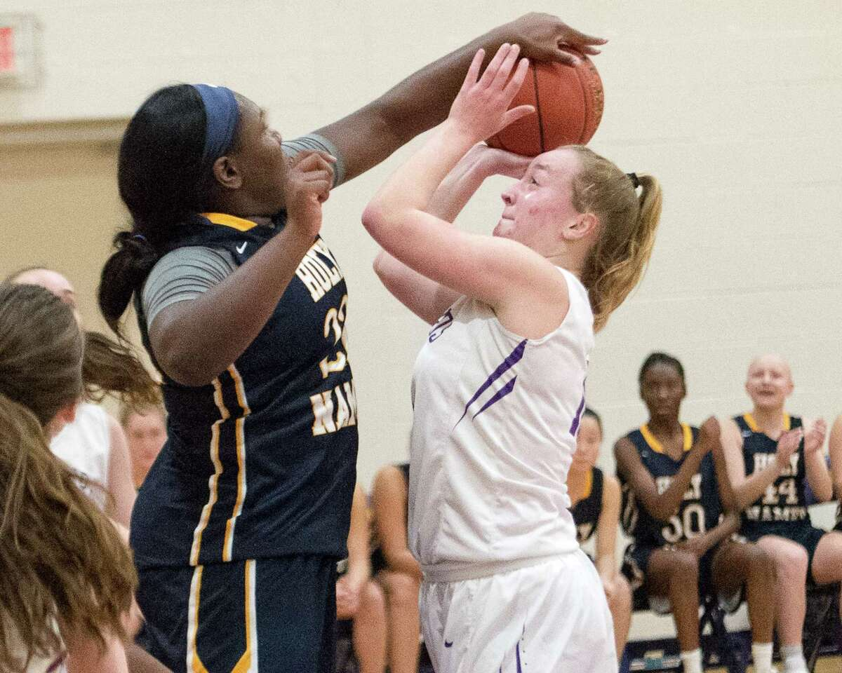 Holy Names senior Saniyya Adams blocks a shot against Voorheesville on Friday, Jan. 4. (Jim Franco / Special to the Times Union)