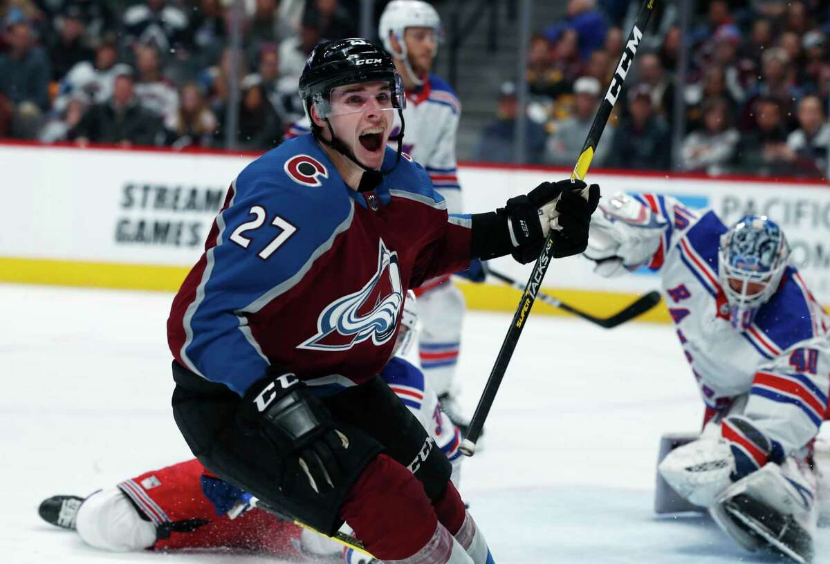 Colorado Avalanche defenseman Ryan Graves, front, reacts after scoring a goal past New York Rangers goaltender Alexandar Georgiev during the third period of an NHL hockey game Friday, Jan. 4, 2019, in Denver. The Avalanche won 6-1. The goal was the first for Graves in the league. (AP Photo/David Zalubowski)