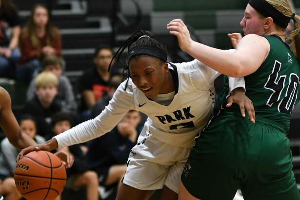 Kingwood Park's Allie Byrd, left, drives to the hoop against a Huntsville defender during the second quarter of their District 20-5A matchup at Kingwood Park High School on January 4, 2019.