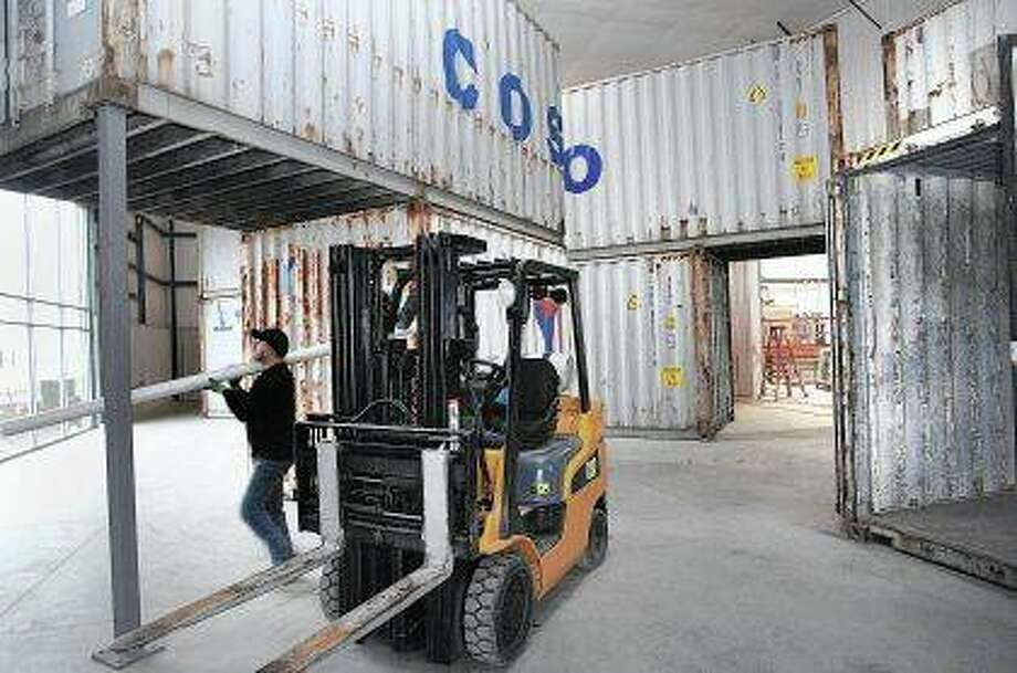Ryan Gentes, a plumber for TCI Plumbing, carries a piece of pipe through a maze of shipping containers that are being recycled into office space at the new headquarters for Zeller Electric in Goodfield. The new office, plant and warehouse building is using a variety of new technologies and recycling ideas to lower cost of operations. Photo: David Proeber | The Pantagraph (AP)