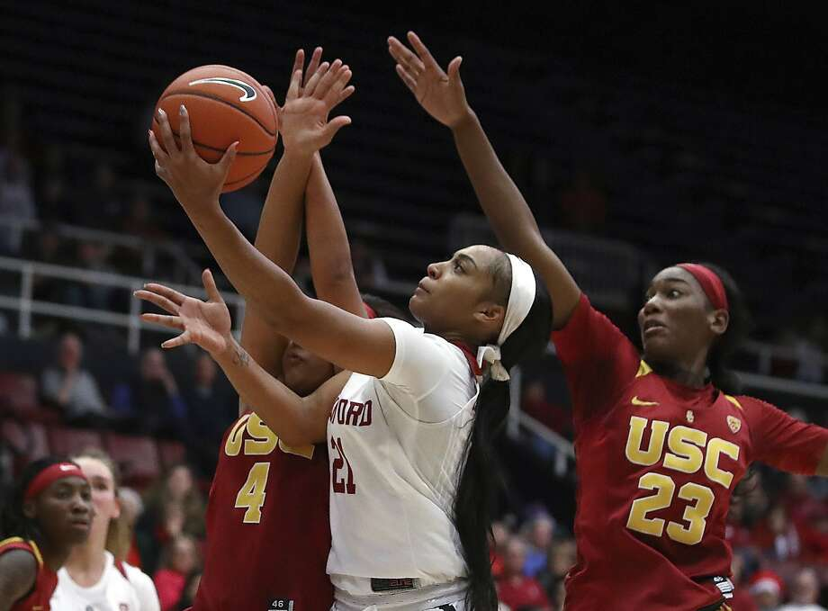 Stanford guard DiJonai Carrington threads a layup between USC's Mariya Moore (4) and Asiah Jones during the Cardinal's victory Friday. It was Stanford's 17th straight home win over USC. Photo: Ben Margot / Associated Press