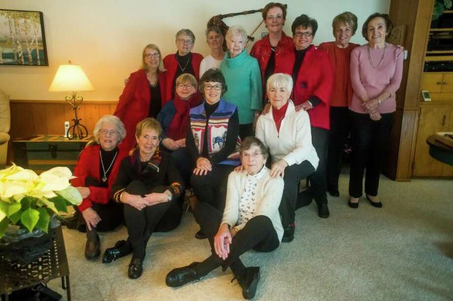 Members of the Happy Bookers book club pose for a photo during a meeting of the group celebrating its 50th anniversary on Tuesday, Dec. 11 in Midland. (Katy Kildee/kkildee@mdn.net)