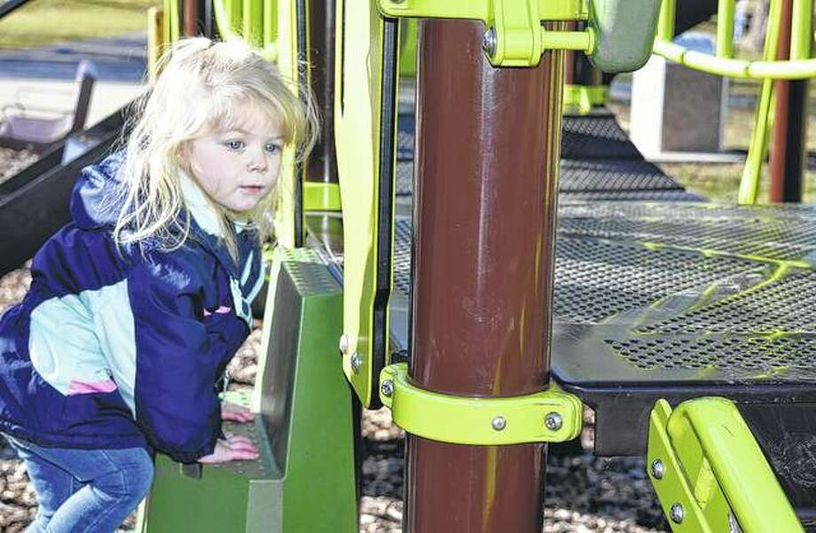 Lilah Rodd, 2, the daughter of Lindsey Lacy of Jacksonville, climbs the play set at Community Park on Friday as she prepares to go down the slide. Photo: Samantha McDaniel-Ogletree | Journal-Courier