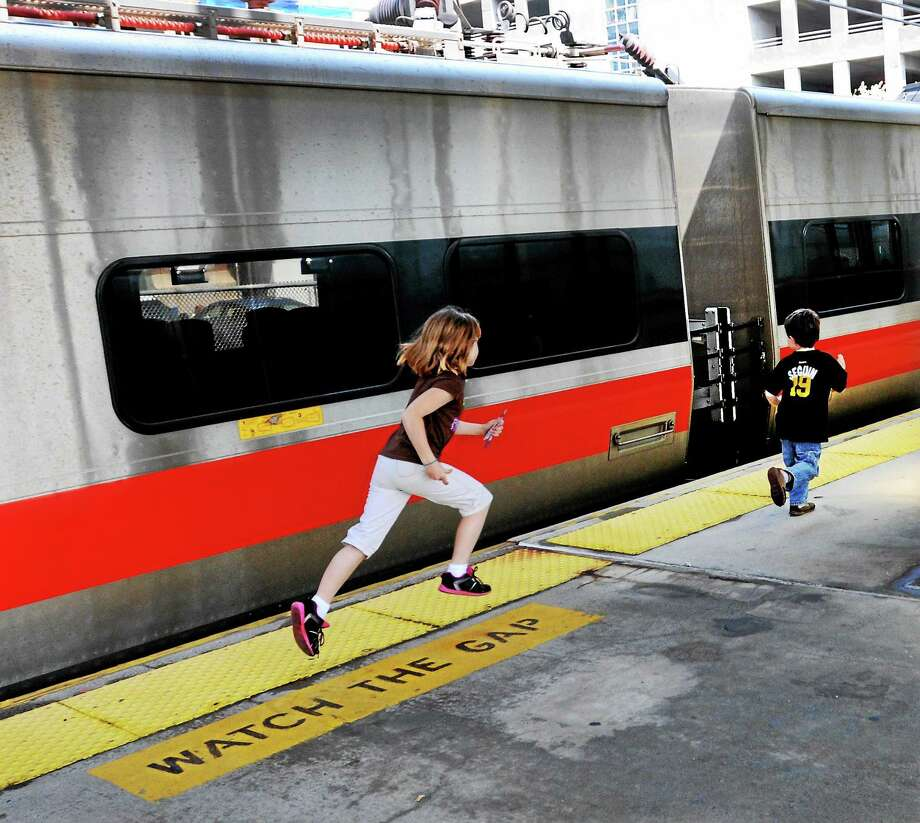 Children run past a static exhibit of a Metro North M8 Electric Multiple Unit train car during a visit to Union Station's celebration of National Train Day in New Haven. Photo: Peter Hvizdak / New Haven Register File Photo / ©Peter Hvizdak /  New Haven Register