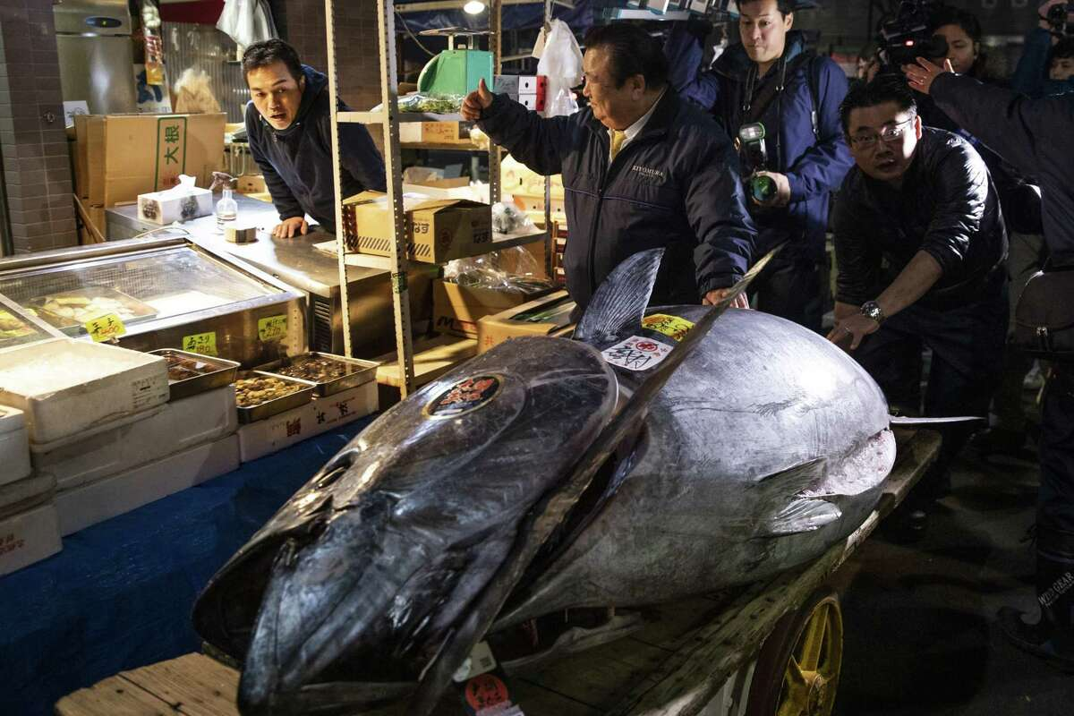 Kiyoshi Kimura, president of Kiyomura Corp., give a thumbs up to a vendor as he walks with a newly-purchased tuna towards a Sushizanmai restaurant in Tokyo, Japan, on Saturday Jan. 5, 2019. Kiyomura, operator of the Sushizanmai restaurant chain across Japan, made the winning bid of 333.6 million yen (about $3.1 million) for a 278-kilogram bluefin tuna at Toyosu Market on Saturday.