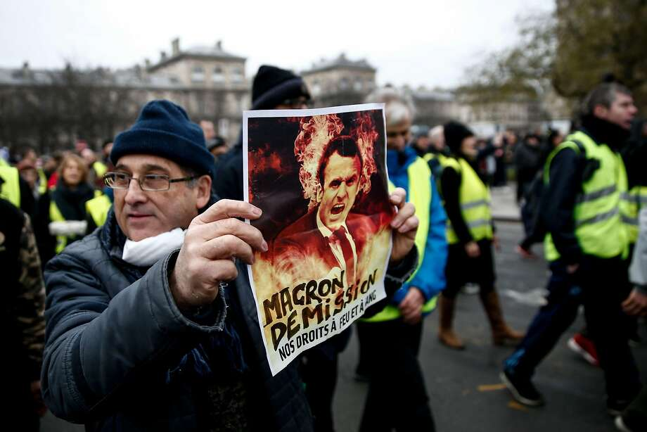 "A demonstrator holds a placard displaying a picture a French President Emmanuel Macron during an anti-government rally organized by the ""yellow vest"" movement in Paris. Photo: Abdul Abeissa / AFP / Getty Images"
