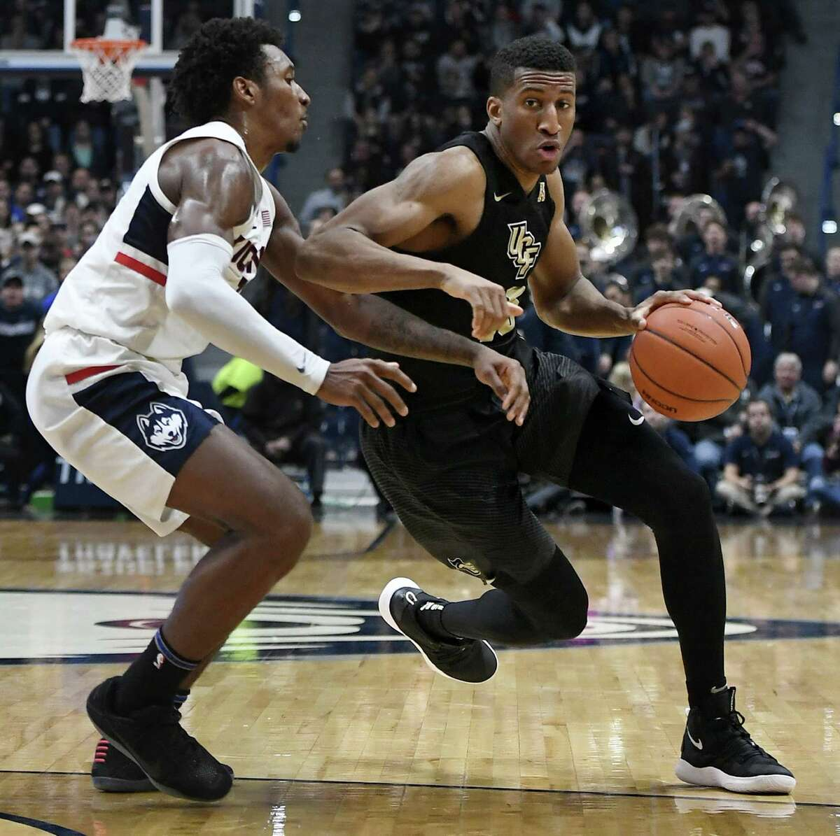 UCF's Aubrey Dawkins dribbles as UConn's Christian Vital defends during the first half on Saturday.