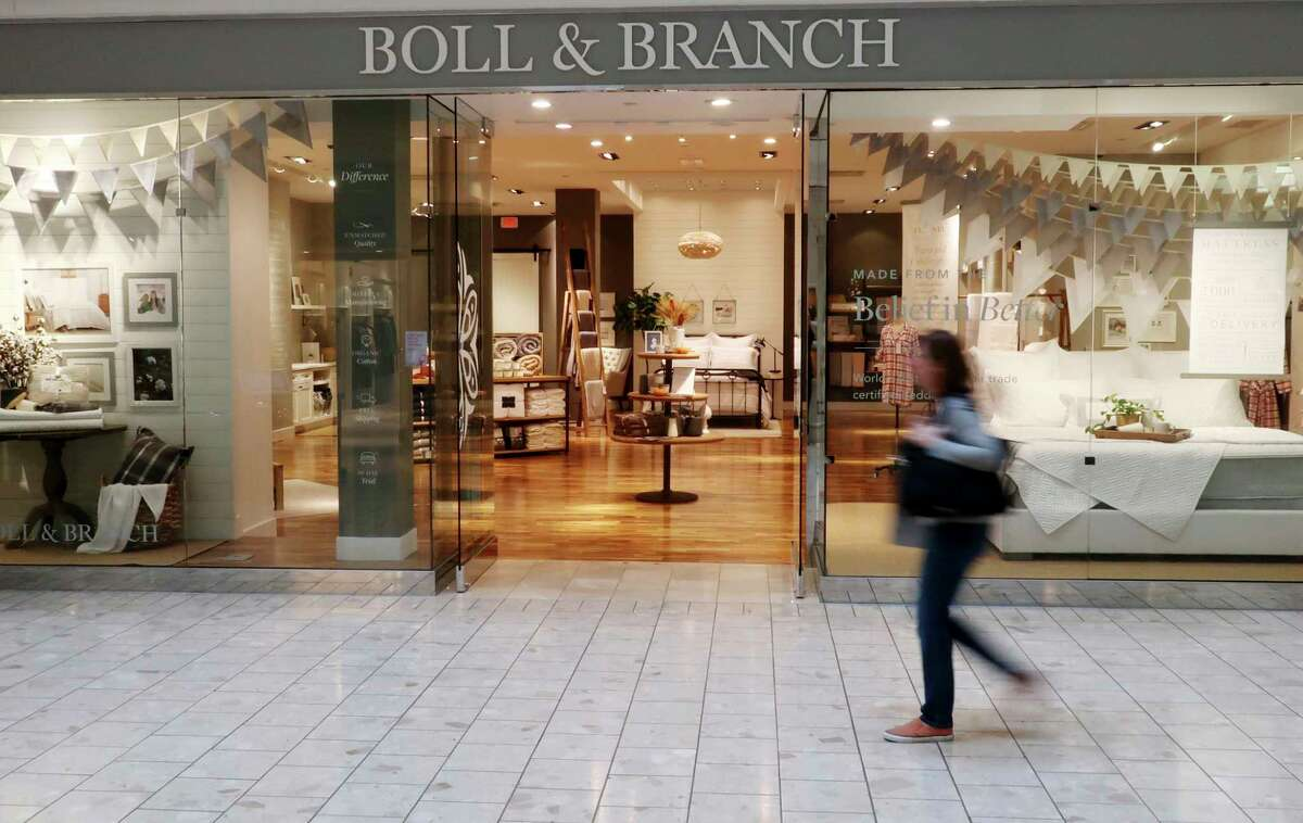 FILE - In this Nov. 2, 2018 file photo, a patron at the Mall at Short Hills in Short Hills, N.J., passes the Boll & Branch furniture store. Shoppers looking for high quality sheets without hurting their budget may want to skip the so-called White Sales at mass retailers. Startups, including Parachute, Brooklinen, and Boll & Branch are cutting out middlemen and selling directly to customers online at a fraction of the price it would normally cost at high-end stores. (AP Photo/Ted Shaffrey)