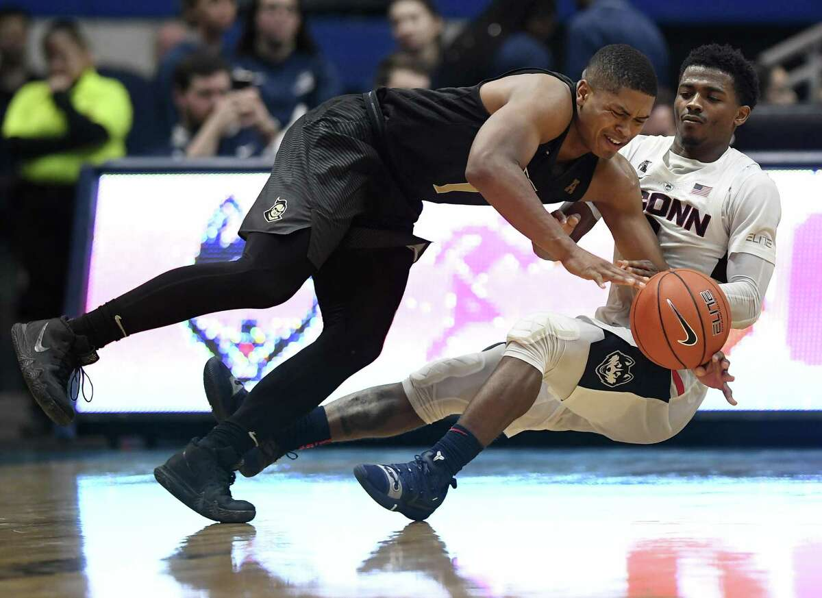 UConn's Alterique Gilbert, right, fouls UCF's BJ Taylor during the second half on Saturday.