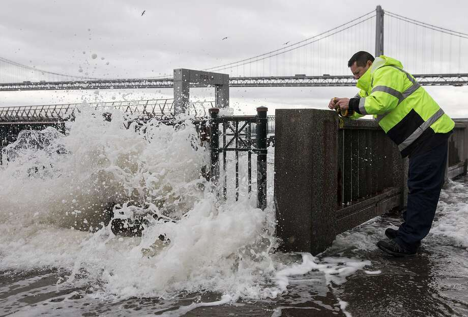 A San Francisco Port Authority worker ties caution tape to Pier 14, closing it off to the public as large waves crash and cause flooding along the Embarcadero in San Francisco, Calif. Saturday, Jan. 5, 2019 as a winter storm moves through the Bay Area. Photo: Jessica Christian / The Chronicle