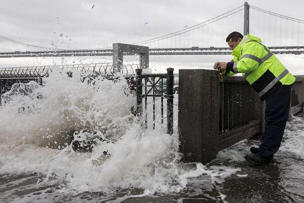 A San Francisco Port Authority worker ties caution tape to Pier 14, closing it off to the public as large waves crash and cause flooding along the Embarcadero in San Francisco, Calif. Saturday, Jan. 5, 2019 as a winter storm moves through the Bay Area.