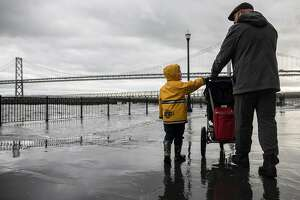 A father and son who wished not to be named watch as large waves crash into Pier 14 along the Embarcadero in San Francisco, Calif. Saturday, Jan. 5, 2019 as a winter storm moves through the Bay Area.